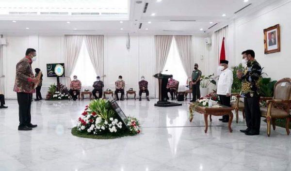 Gubernur Olly saat menerima penghargaaan yang diserahkan langsung oleh Wapres RI. (Foto.ist)