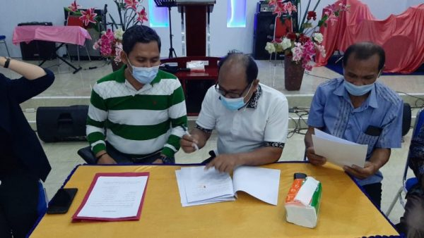 Direktur LBH Manguni Indonesia, Vebry Tri Haryadi bersama Pendeta Hipterk Haniko melakukan kesepakatan dan penandatanganan kuasa hukum.