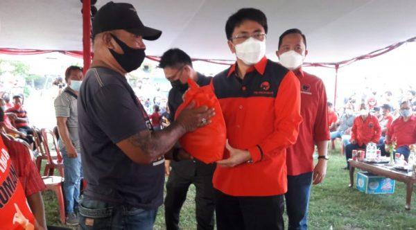 Walikota Andrei Angouw selaku Bendahara PDIP Provinsi Sulut didampingi, Ketua DPC PDI-P Kota Manado dr Richard Sualang memberikan secara simbolis Bansos kepada salah satu nelayan
